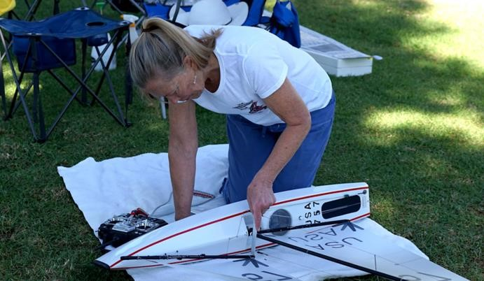 Gene Harris is shown tuning her V9 with a scale in millimeters, the class standard reference. Before she is done here the mainboom will be on or near centerline. On the last day I caught Zvonko measuring his shroud tension, as he said he had a tune he liked so he recorded it. The ability to repeat fast settings is de rigueur in this class. Robert Hirsch photo.